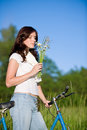 Woman with old-fashioned bike and summer flower Stock Photo