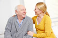 Woman and old man in retirement senior men home smiling at each other Royalty Free Stock Image