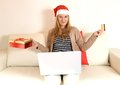Woman online christmas shopping with computer and credit card young Royalty Free Stock Image