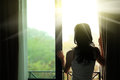 Woman opening curtains in a bedroom young morning after rain Stock Photography