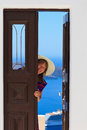 Woman opening door to the sea welcome santorini concept Stock Photos