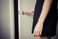 Woman opening a door to the unknown young is into Royalty Free Stock Images