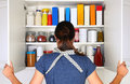 Woman opening full pantry a seen from behind the doors to a fully stocked the cupboard is filled with various food stuff and Royalty Free Stock Image
