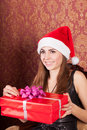 Woman opens a christmas gift attractive girl in hat Royalty Free Stock Photo