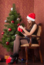 Woman opens a christmas gift attractive girl in hat Royalty Free Stock Photography