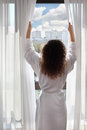Woman opens curtains and looks up Stock Image