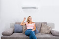 Woman Operating Air Conditioner With Remote Control Royalty Free Stock Photo