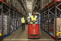 Woman operating tow tractor in a busy distribution warehouse Royalty Free Stock Photo