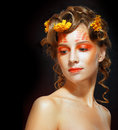 Woman with orange artistic visage autumn make up beautiful young and hairstyle on dark background Stock Photography