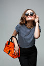 Woman with orange bag in studio. sunglasses, Royalty Free Stock Photo