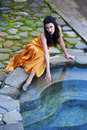 Woman in an orange dress sitting by the pool Royalty Free Stock Photo