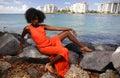 Woman in orange posing on the rocks Royalty Free Stock Photo