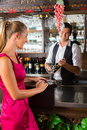 Woman ordering glass of wine at bar Royalty Free Stock Photos