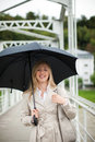 Woman out walking in the rain smiling as she shelters under her umbrella her stylish beige raincoat Royalty Free Stock Photo