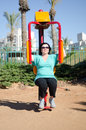Woman at the outdoor gym working out on a butterfly machine mature in sunny day Royalty Free Stock Image