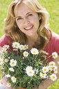 Woman outdoors holding flowers smiling Stock Photo