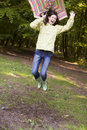 Woman outdoors jumping with umbrella smiling Royalty Free Stock Image