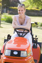 Woman outdoors with lawnmower smiling Royalty Free Stock Photo