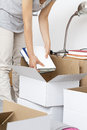 Woman packing books a putting into a cardboard box Royalty Free Stock Photo