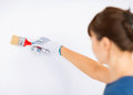 Woman with paintbrush colouring the wall Stock Images