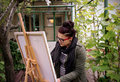 Woman painter in work is painting with brush garden Stock Images