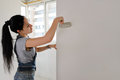 Woman painting an apartment wall finishing off the redecorating with a paintbrush Royalty Free Stock Photos