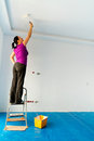 Woman painting ceiling Royalty Free Stock Photos