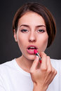 Woman painting her lips Stock Images