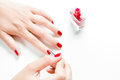 Woman painting her nails with red nail polish Royalty Free Stock Photo