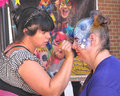 Woman painting a person's face doing on another woman's taken on august on yonge street in toronto ontario during the Royalty Free Stock Photo