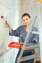 Woman paints wall at home Stock Photo