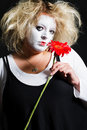 Woman pantomime with a red flower on black background Royalty Free Stock Image