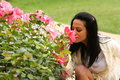 Woman in a park smelling blossom of roses bush outside Royalty Free Stock Photos