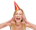 Woman in party cap shouting through megaphone shaped hands Stock Photo