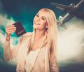Woman with passport against blue sky with plane happy blond Stock Image