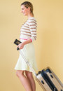 Woman with passport and suitcase walking against colored backgro side view of young background Royalty Free Stock Photo