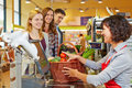 Woman paying groceries at young women basket of supermarket checkout Stock Photo