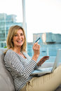 Woman paying on internet with her credit card sofa Royalty Free Stock Photography