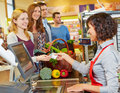 Woman paying with money bill at smiling women cash euro supermarket checkout Stock Photo