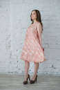 Woman in a peach dress against the white brick wall Royalty Free Stock Photo