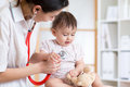 Woman pediatrician examining of baby kid with stethoscope women in office Royalty Free Stock Photos
