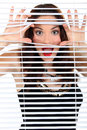 Woman peeking through blinds closed Royalty Free Stock Images