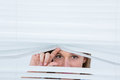 Woman peering through roller blind on white background Stock Image