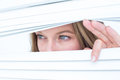 Woman peering through roller blind Royalty Free Stock Photo