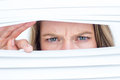 Woman peering through roller blind on white background Stock Photo