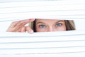 Woman peering through roller blind on white background Royalty Free Stock Images