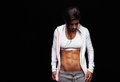 Woman with perfect abdomen muscles in sportswear portrait of a fit young muscular female athlete looking down on black background Stock Photo