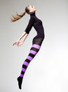 Woman with perfect body jumping dressed in purple striped tights and black top Stock Photography