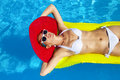 Woman with perfect tanned body lying on yellow air mattress in t young pretty the pool Royalty Free Stock Images