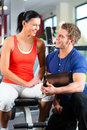 Woman and personal trainer in fitness gym with her the Royalty Free Stock Photo